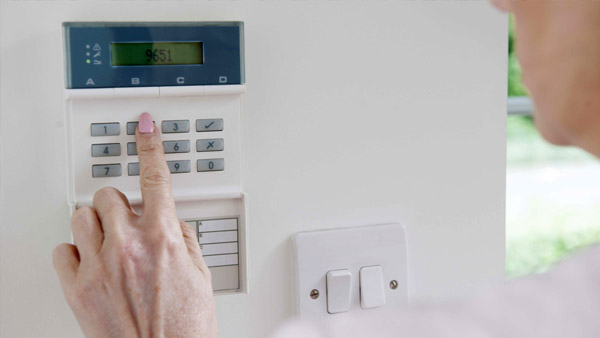 Woman Setting Control Panel On Home Alarm System