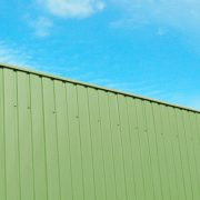 Green Colorbond Steel Fence Against a Blue Sky