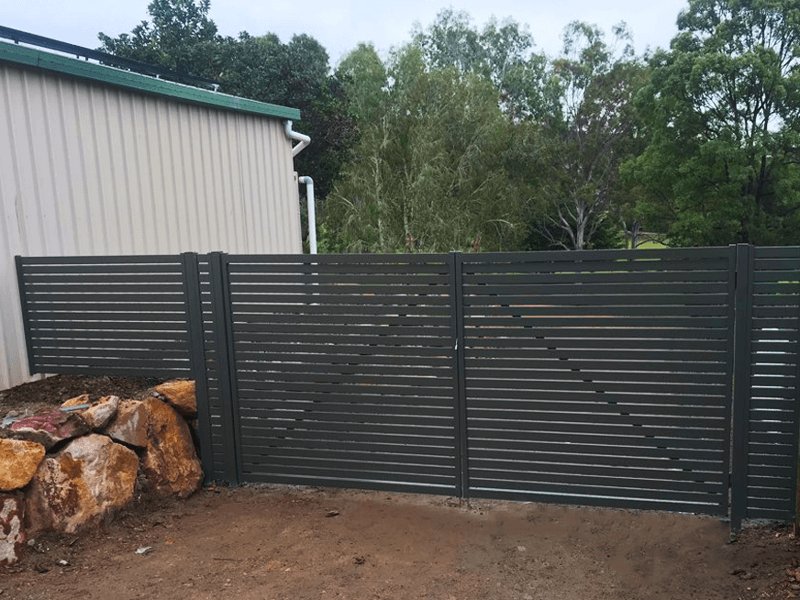 Aluminium slat fencing and gate on rock retaining wall and driveway